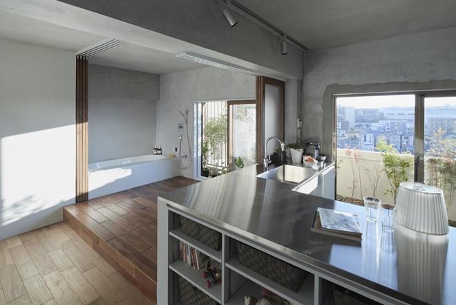 Đảo bếp kết hợp làm tủ để sách và ngăn cách khu nấu nướng với các không gian khác.