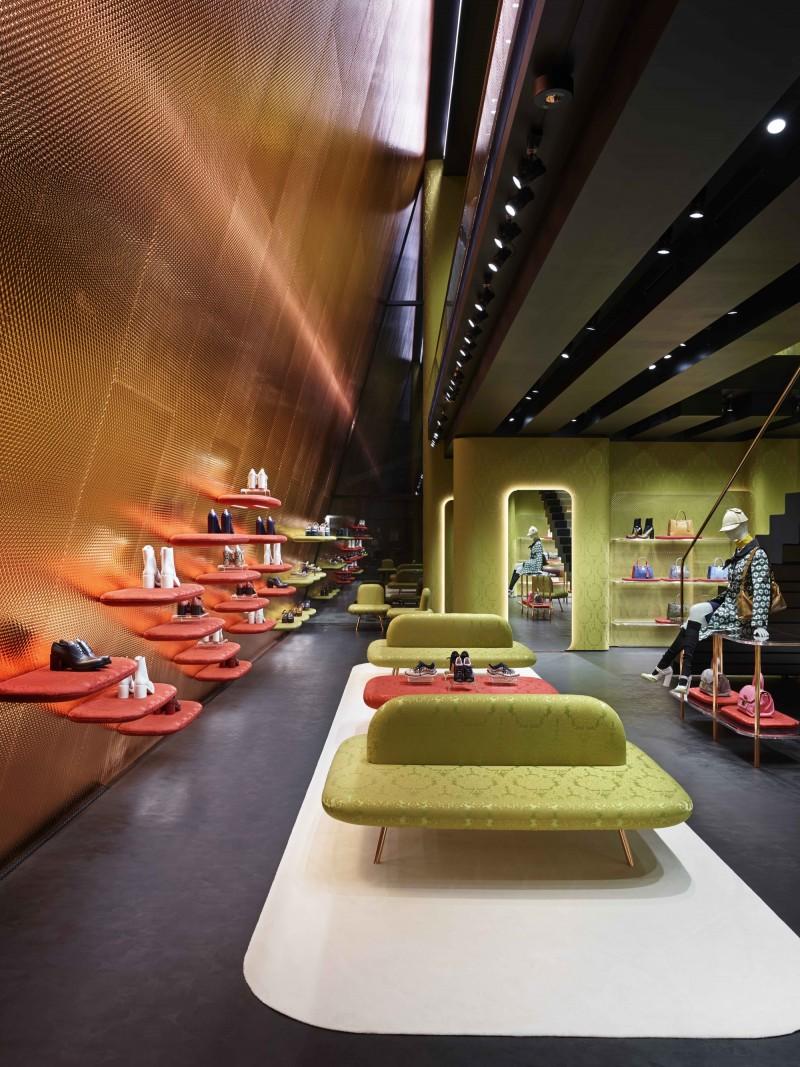 """Trên cùng con phố với dự án Prada Store năm 2003, Herzog & de Meuron đã tiếp tục thiết kế Miu Miu Aoyama Store với tinh thần nhằm tạo sự khác biệt rõ ràng với công trình cũ. Cùng tọa lạc ngay tại khu vực trung tâm thời trang của Aoyama (Tokyo, Nhật Bản), hai cửa hiệu Prada và Miu Miu Aoyama đều có phong cách kiến trúc ấn tượng. Các KTS đã giải thích về sự """"không thống nhất"""" trên phố Miyuki của hai công trình với chiều cao và hình dáng khác nhau, không tuân theo truyền thống lịch sử hay tiêu chuẩn chung nào là do cảnh quan tại đây sẽ không thể trở thành một không gian thật sự nếu thiếu sự thu hút như một đại lộ hay quảng trường"""". Trong khi Prada Store bổ sung sự thu hút ấy bằng bề mặt trong suốt và quảng trường công cộng thì Miu Miu Store lại giảm thiểu nội thất tại những khu vực công cộng cùng với bề mặt vật liệu đục và chỉ ngăn cách bởi những bức tường phía trước. Cửa hiệu Miu Miu hai tầng đã được thiết kế trên nguyên tắc """"Giống như một ngôi nhà hơn là một gian hàng, nhiều không gian kín hơn mở, nhiều sự tinh tế hơn xa hoa, nhiều sự mờ đục hơn trong suốt"""". Nhìn chung, Miu Miu Aoyama Store là một ví dụ hiếm hoi của các KTS trong việc nhìn nhận lại tư tưởng thiết kế trong kiến trúc và nhận định rằng luôn có hai (hoặc nhiều hơn) những cách khác nhau để tiếp cận một vấn đề hóc búa trong kiến trúc."""
