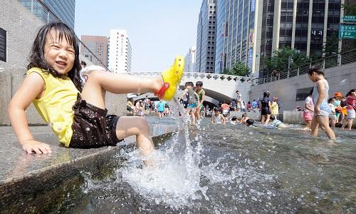 Bé gái nghịch nước tại suối Cheonggyecheon ở trung tâm Seoul. Ảnh: Park Ji-Hwan