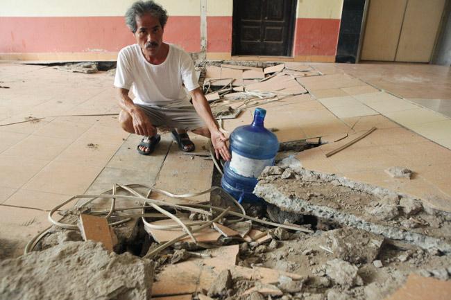Ông Đoàn Văn Dũng (52 tuổi) sống ở khu nhà N5 lấy bình nước đo độ sụt lún của nền nhà trước khi bị sập và sau khi bị sập