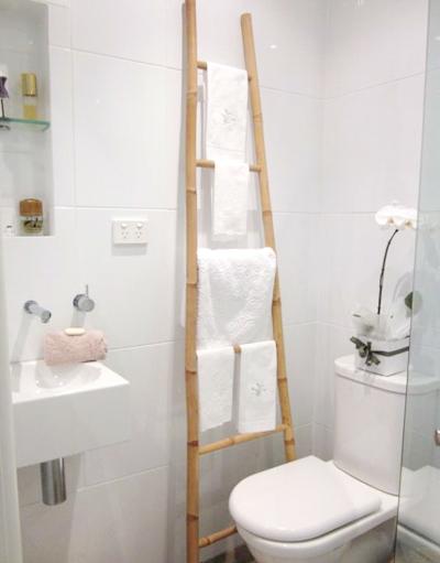 Nếu không muốn đóng thêm tủ cho phòng tắm chật, bạn có thể sử dụng chiếc thang tre để treo khăn.