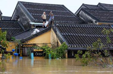 Người dân leo lên mái nhà cầu cứu ở Hội An - Ảnh Reuters