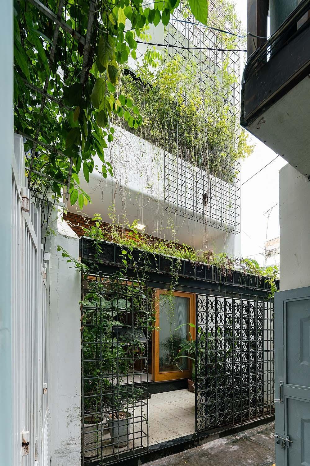 """Mặt tiền công trình gây ấn tượng với cổng """"hoa sắt"""", giàn leo và cây xanh trên nền tường trắng. Ảnh: Quang Trần."""