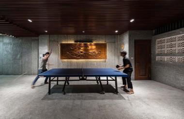 Bàn bóng bàn tạo thành điểm nhấn đặc biệt trên nền màu trắng xám của sàn, tường làm từ đá chẻ và màu nâu của trần gỗ.