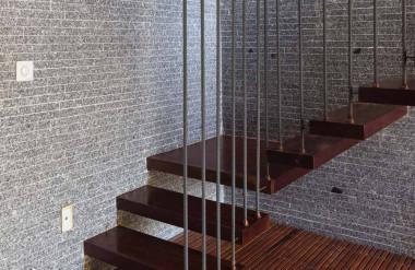 Cầu thang bậc rỗng làm từ sắt và gỗ dẫn từ tầng trệt lên tầng hai.