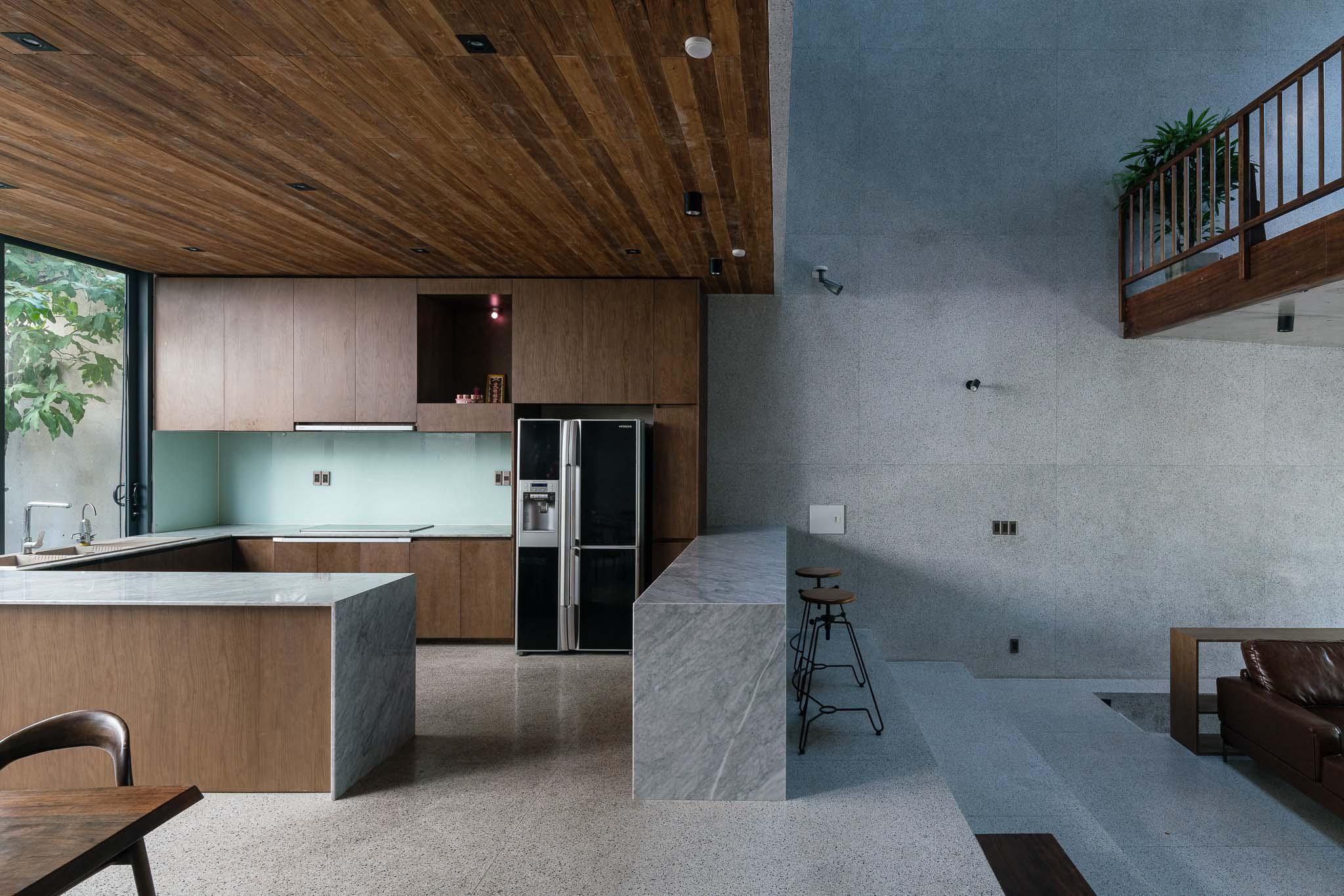Bếp nằm phía sau phòng khách. Sự thay đổi về chiều cao tạo nên ranh giới giữa các không gian chức năng.