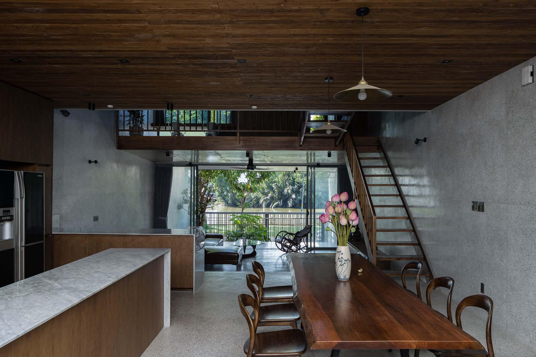 Nhờ ô cửa lớn ngoài phòng khách và giải pháp thay đổi độ cao, gia chủ ở trong bếp vẫn dễ dàng ngắm nhìn con sông trước nhà.