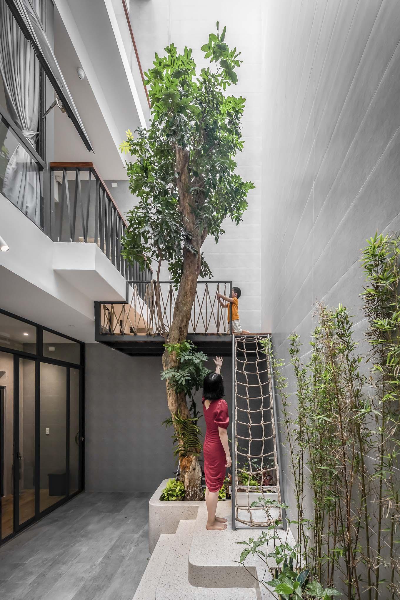 Nhờ giản lược không gian không cần thiết, căn nhà có thể chừa ra khoảng thông tầng lớn sau nhà để làm chỗ thư giãn kết hợp nhà trên cây để cả người lớn lẫn trẻ con có thêm chỗ thư giãn. Ảnh: Minq Bui Photography.
