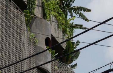 Màu xám của bê tông kết hợp với tường thông gió bằng cemboard tạo điểm nhấn ở mặt tiền.