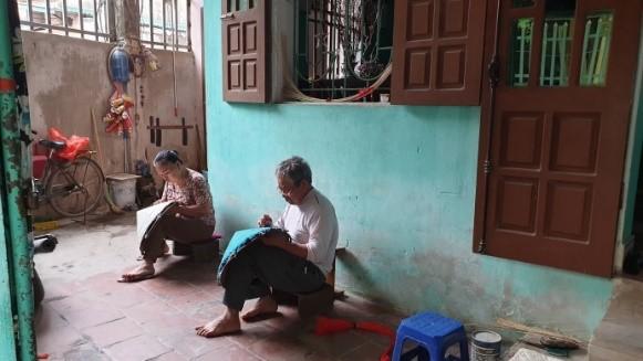 Đàn ông và phụ nữ cùng thắt nón ở hiên nhà