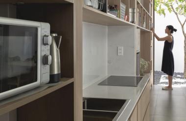 Hệ kệ biến không gian nhà trở nên đa dụng. Hành lang vừa là lối đi vừa là chỗ nấu nướng, giặt giũ.