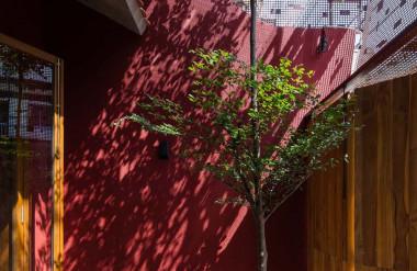 ...nhưng vẫn giữ được sự thông thoáng. Ánh nắng khi đi qua khung thép còn tạo nên hiệu ứng lên bức tường đỏ.