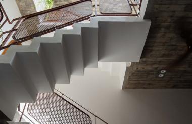 Khoảng thông tầng kết hợp với cầu thang nằm ở giữa nhà, bên trên là mái kính. Lan can cũng làm bằng thép, tạo sự đồng nhất trong thiết kế với mặt tiền và mái.