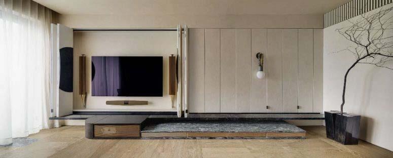 TV và một lối đi nằm phía sau các tấm thạch cao. Một tấm đồng bị oxy hóa đã được gắn vào các tấm đôi tăng lên như một tay cầm mở tủ TV